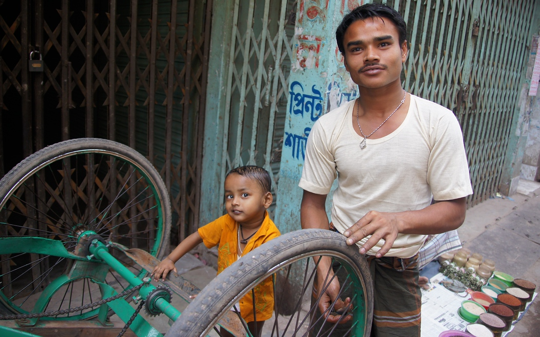 A man and his cute son smile as they repair a decommissioned rickshaw - Old Dhaka, Bangladesh.