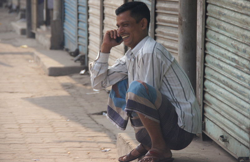 This is a candid shot of a man squatting down and enjoying a conversation on the cell phone as he radiates a big grin - Old Dhaka, Bangladesh.