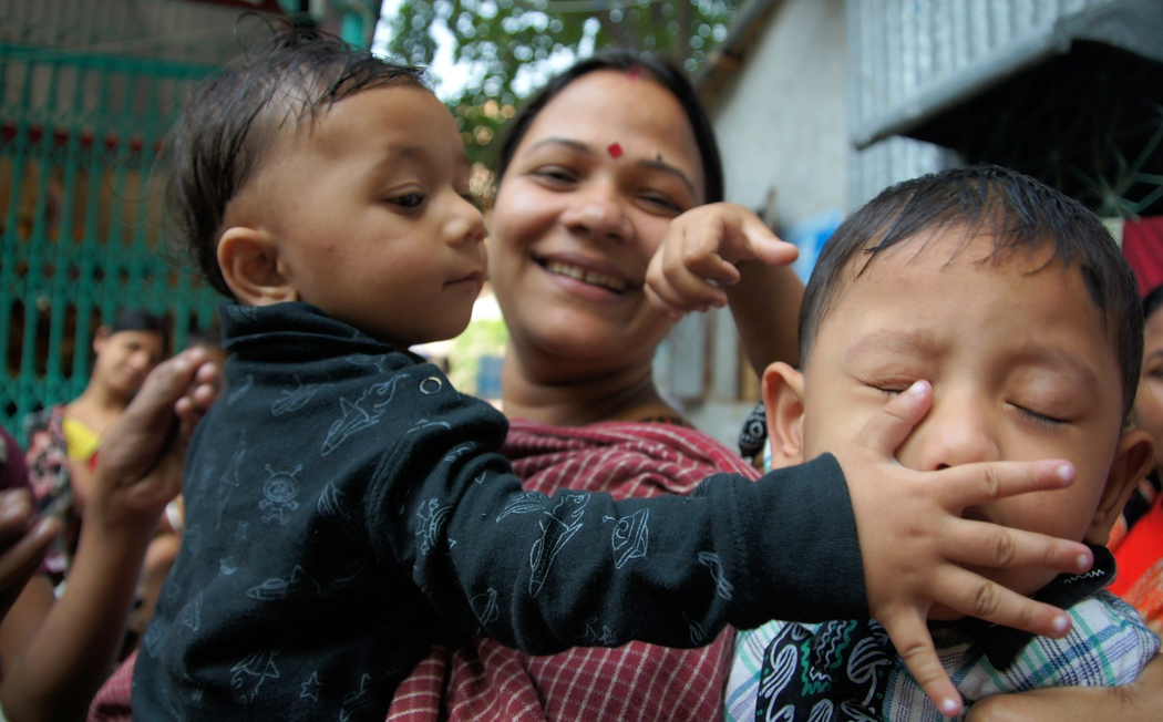 I was invited by a group of Bangladeshi men (who were playing impromptu tour guide) to join them for a festival involving children playing.  In this photo a younger brother is sticking his hand in the face of his older brother while his mother smiles.