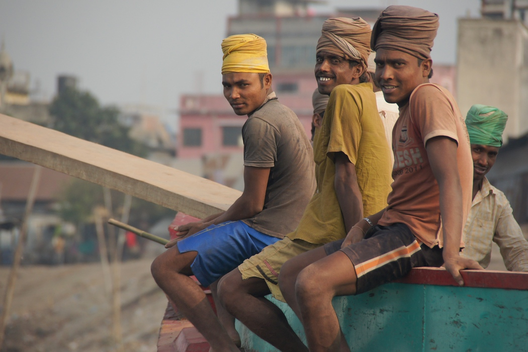 A group of friendly locals smiling as they boarded a larger vessel on the Buriganga river - Old Dhaka, Bangladesh.