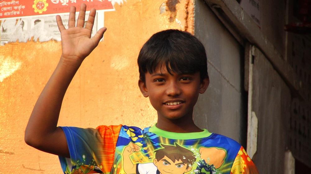 A cute Bangladeshi boy waves hello to me.
