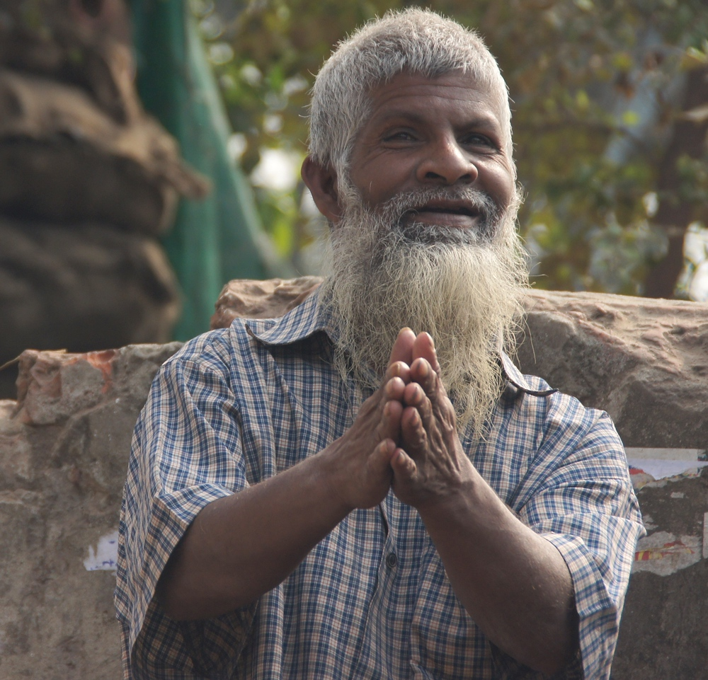 This jolly looking Bangladeshi man with a distinctly long white beard clasps his hands together and smiles.