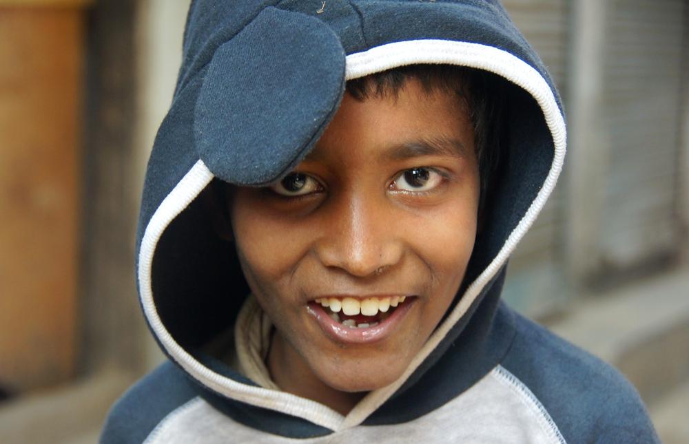 This Bangladeshi boy wearing a hoody flashes a distinct smile.