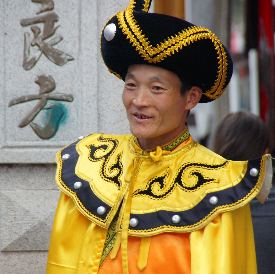 A Chinese man dressed in an elaborate regional costume and headdress smiles in Dali, China.