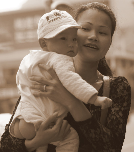 This Chinese lady flashes a smile while glancing out of the side of her eyes at the child she is carrying in her arms - Yangshuo, China.