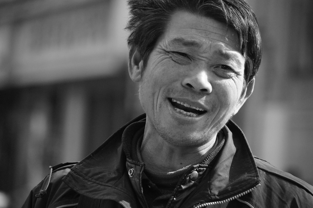A captured this candid portrait of a Chinese man smiling while walking in one of the more hectic areas of Shanghai, China.