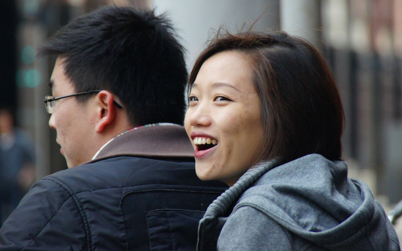 This Chinese lady smiles while hopping on the back of a motorbike in Shanghai, China.