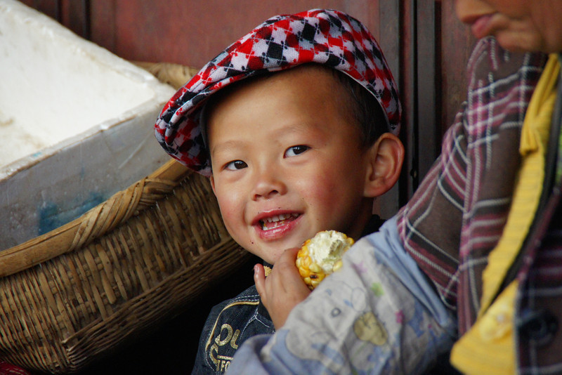This cute little boy - wearing a poorboy cap - was smiling at me while taking a break from eating his section of corn on the cob in Lijiang, China.