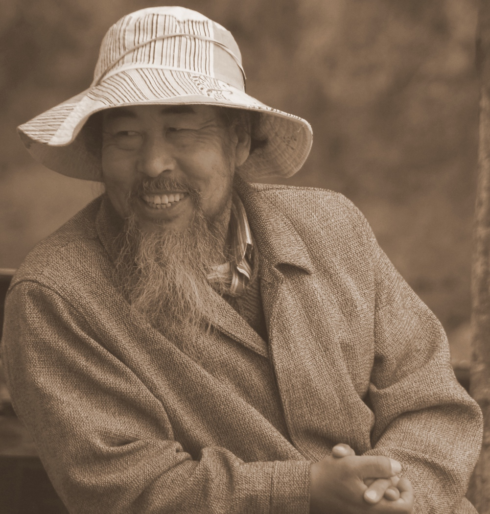 This Chinese man with a distinct long beard and sunhat shares a laugh with a friend on a park bench in Dali, China.