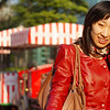 A Chinese lady wearing a vermilion color leather jacket walks down the street in Shanghai, China while talking on the phone.