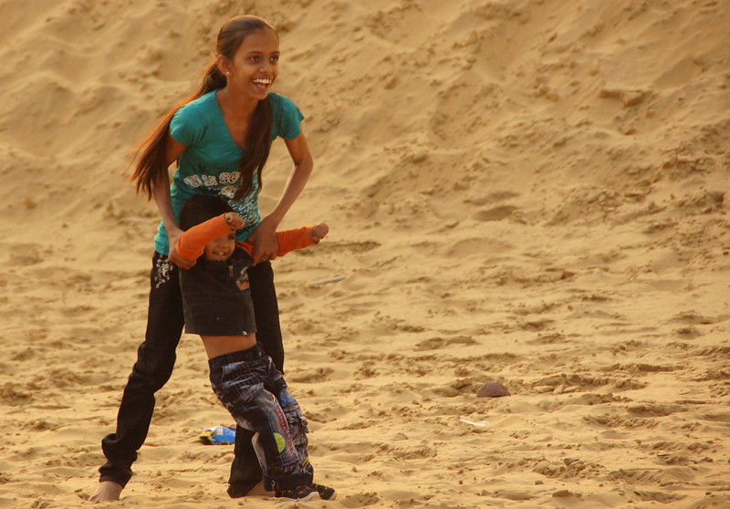 A cute little girl plays with her smaller brother at the Sam sand dunes located outside of Jaisalmer - Rajasthan, India.