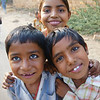 A group of adorable children look up at the camera and flash some genuinely lovely smiles.  Travel photo from the Thar Desert - Rajasthan, India.
