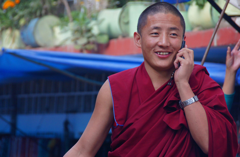 A Tibetan monk in exile (located in Mcleod Ganj) talks to somebody on his cellphone.  Dharamsala, India.