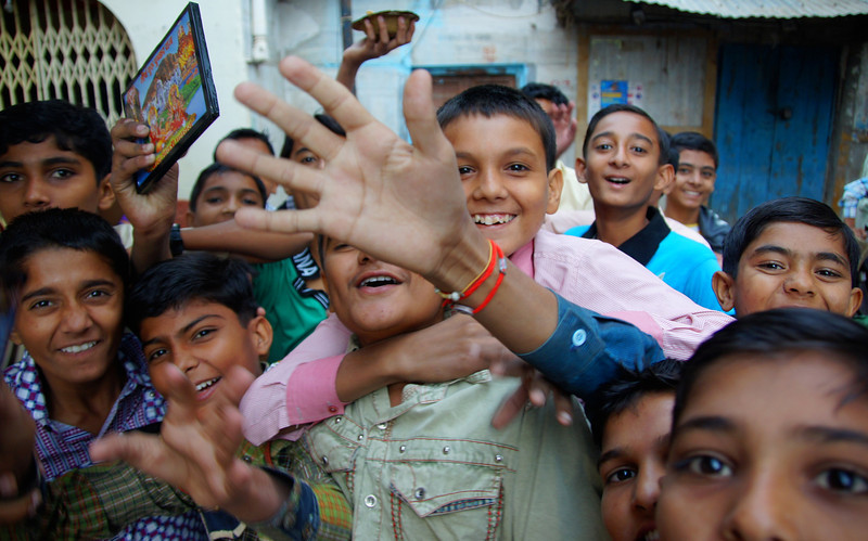 A group of excited India boys grin and move closer towards my camera as I try my best to compose a shot.  Travel photo from Pushkar - Rajasthan, India.