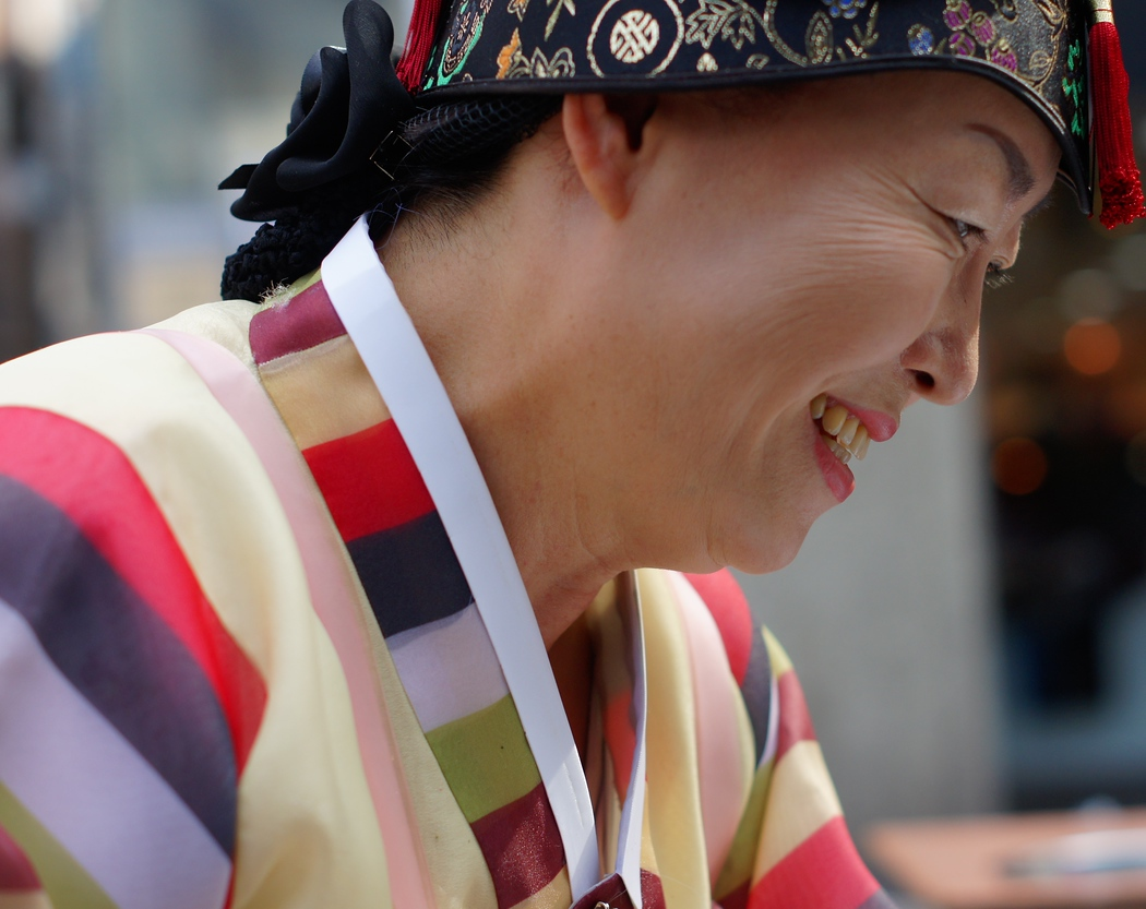 An elderly Korean lady radiating a warm smile to her customer as she prepares some Korean traditional food in Insadong - Seoul, South Korea.