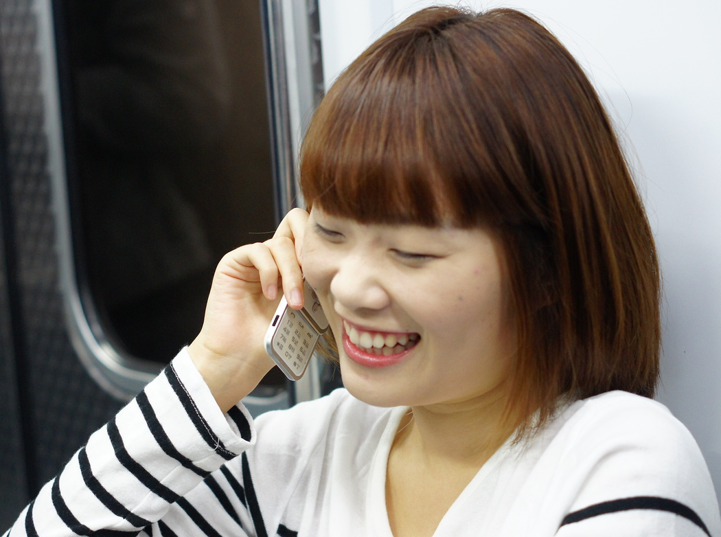 A candid moment with a lady having what appears to be a very happy and possibly humorous conversation on her cell phone as she rides the Metro in Seoul, South Korea.