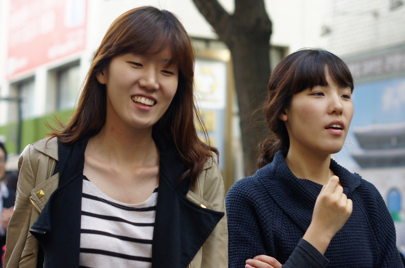 A photo of two Korean ladies grinning as they walk down the popular tourist cultural district of Insadong - Seoul, South Korea.