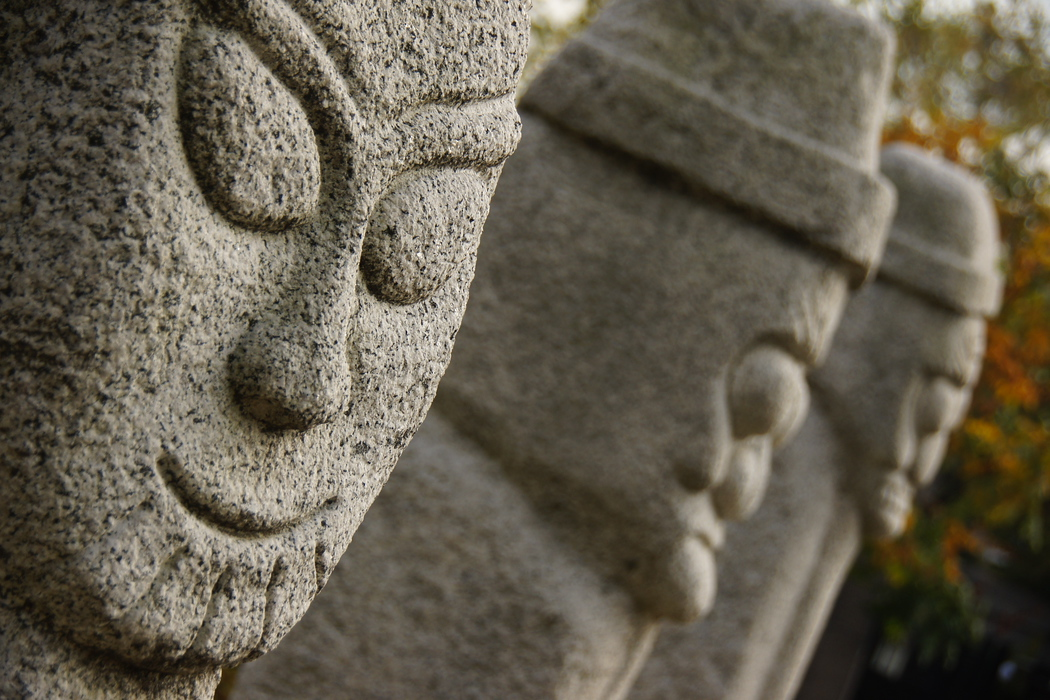 A travel photo of some smiling statues/sculptures/totem poles located in Gyeongbokgung Palace - Seoul, South Korea.