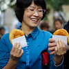 A lady walking down the street with a Korean sweet filled pancake (known locally as hotteok) - Seoul, South Korea.