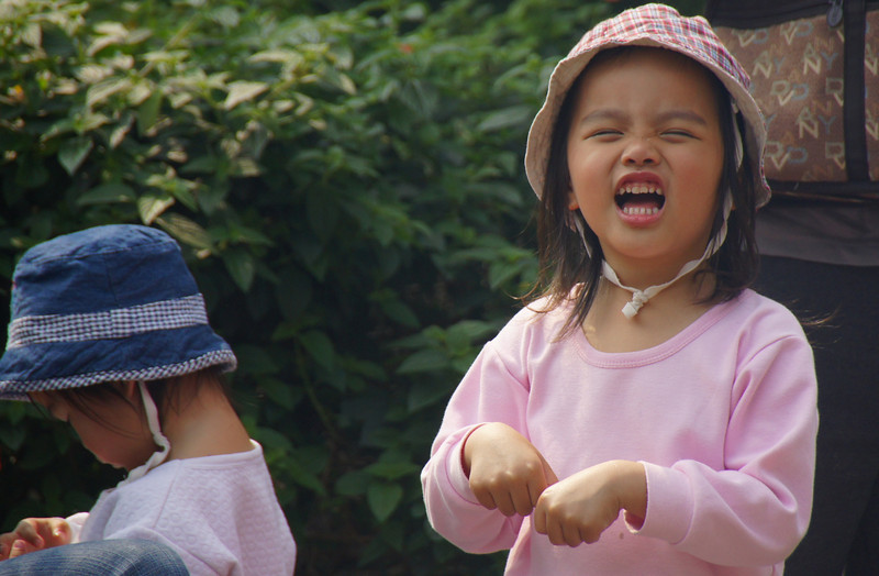 This cute girl radiates a joyous smile as she enjoys playing with some friends at Danshui - New City Taipei, Taiwan.