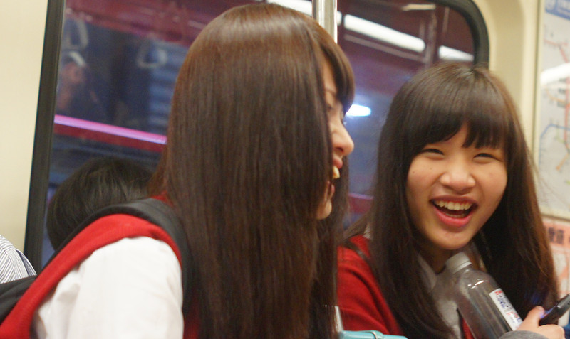 These two schoolgirls giggle hysterically on the metro - Taipei, Taiwan.