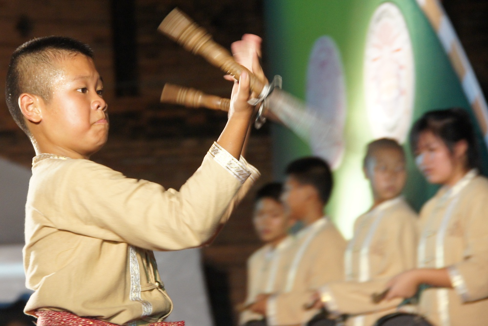 A Thai boy wielding small swords in his hands has an intense look in his eyes.