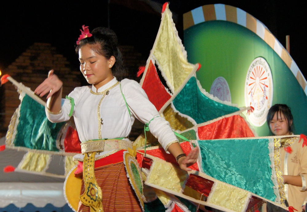 A Thai teenager blissfully dances around the stage while smiling.