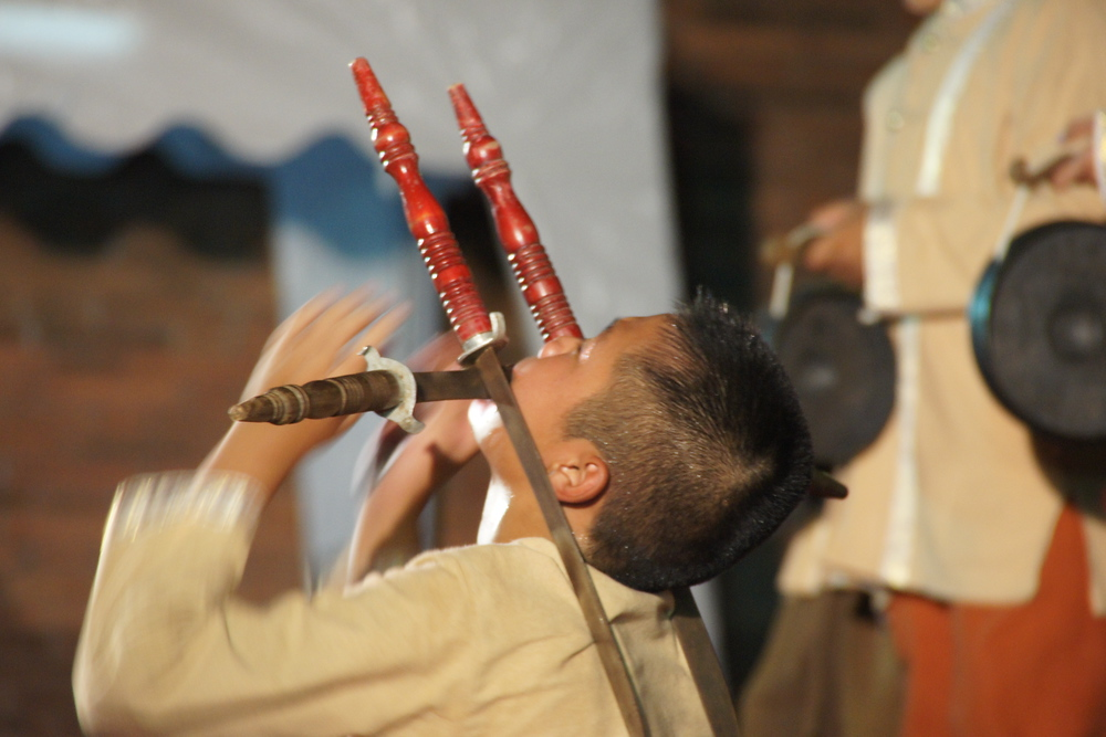 A photo that captures the motion blur of a Thai boy holding a sword in his mouth.