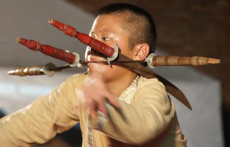 A Thai teenage boy supporting several swords in his mouth performs coordinated martial arts manoeuvres that were simply phenomenal.