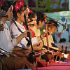 A close up shot of some Thai performers and the traditional instruments they are using.