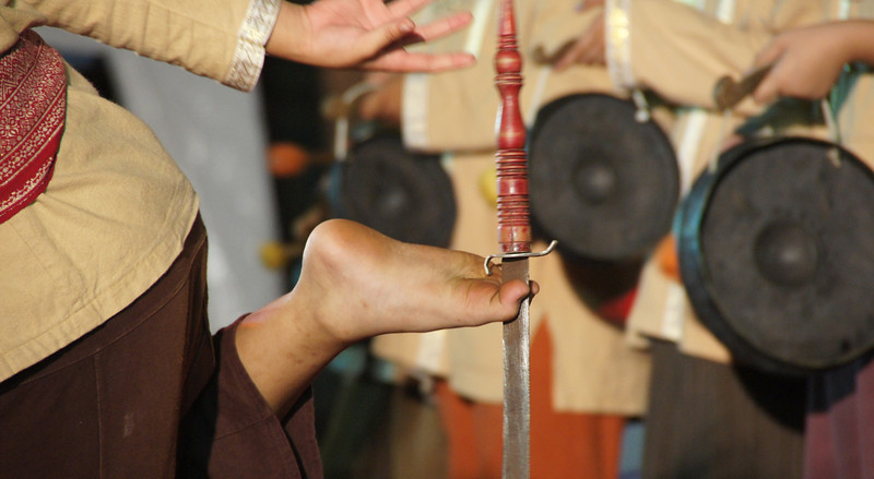 A close-up shot of a Thai boy performing martial arts stunts with a dagger in between his toes.