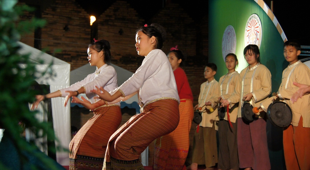 Two Thai girls dressed in traditional attire dance flawlessly with grace.