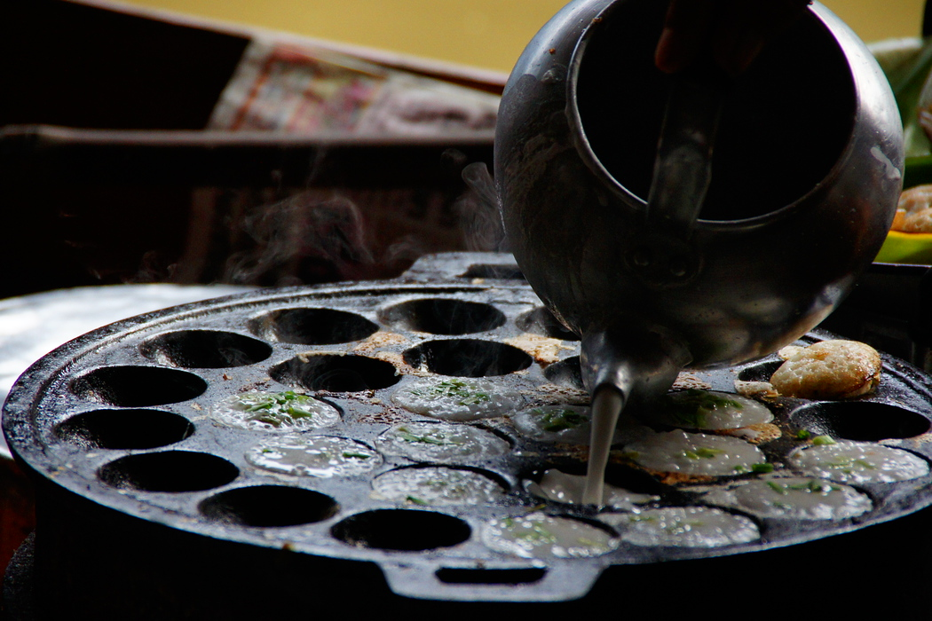 Batter is being poured into a mold being used to make Thai cakes.