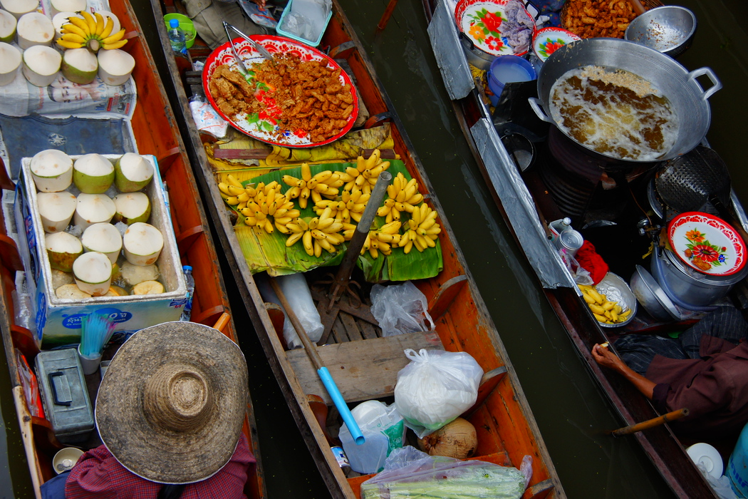 An overhead perspective travel photo of three rowboats filled with fruit (bananas and coconuts) passing each other at the same time.