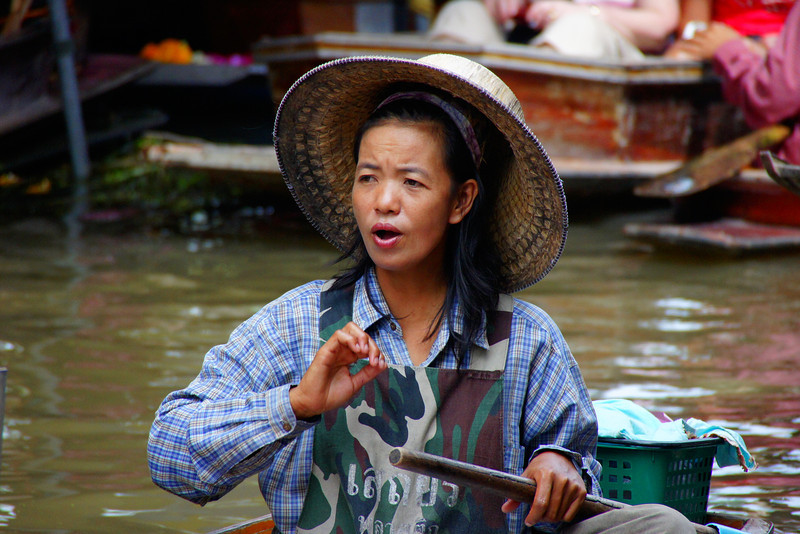 A candid photo of a Thai lady wearing a conical hat and army fatigue inspired apron.