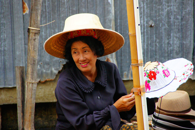 A Thai lady vendor with a collection of hats for sale flashes a smile.