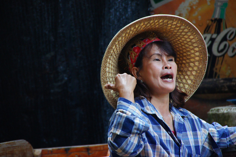 A candid moment, where this Thai lady is communicating with another vendor at the floating market.