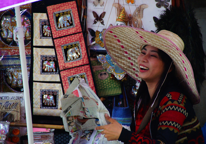 A Thai lady wearing a distinctly large sun hat laughs while folding a newspaper.