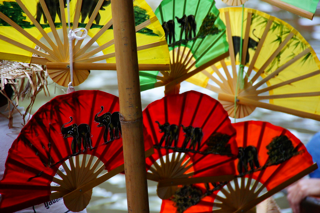 Colorful fans for sale with elephant patterned designs.