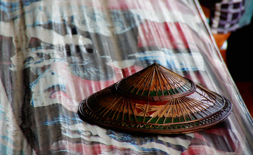 A Thai conical hat for sale on an otherwise bare display table.