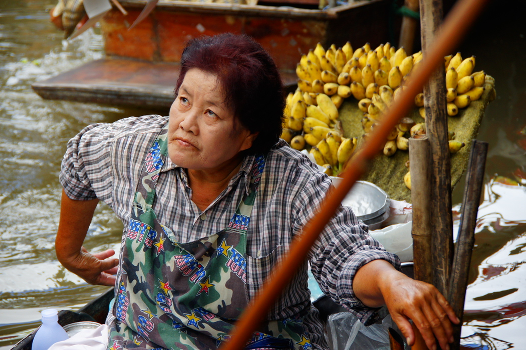 A Thai lady with dyed hair makes eye contact with a group of tourists.