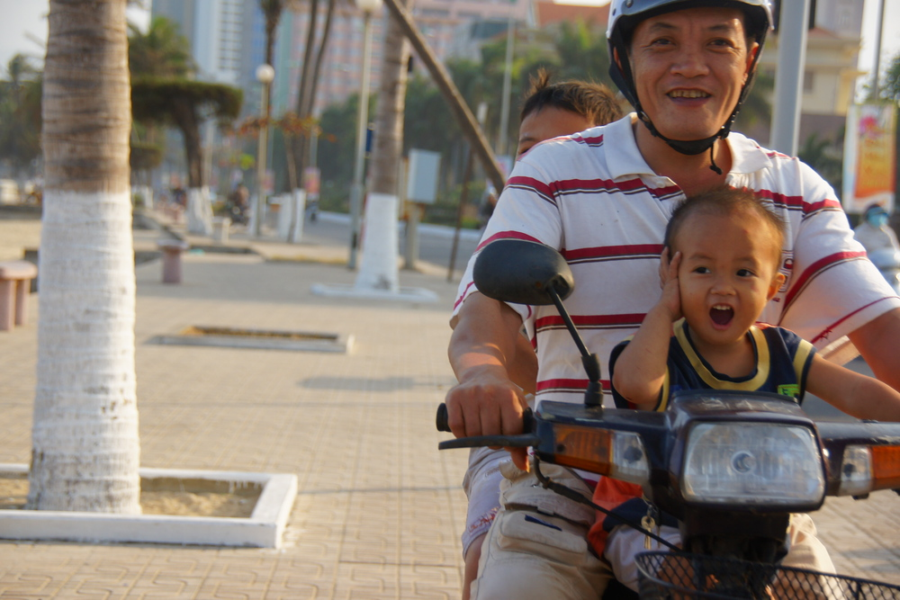 A boy in total glee enjoys every moment of being on a scooter with the rest of his family as they all smile at me - Nha Trang, Vietnam.