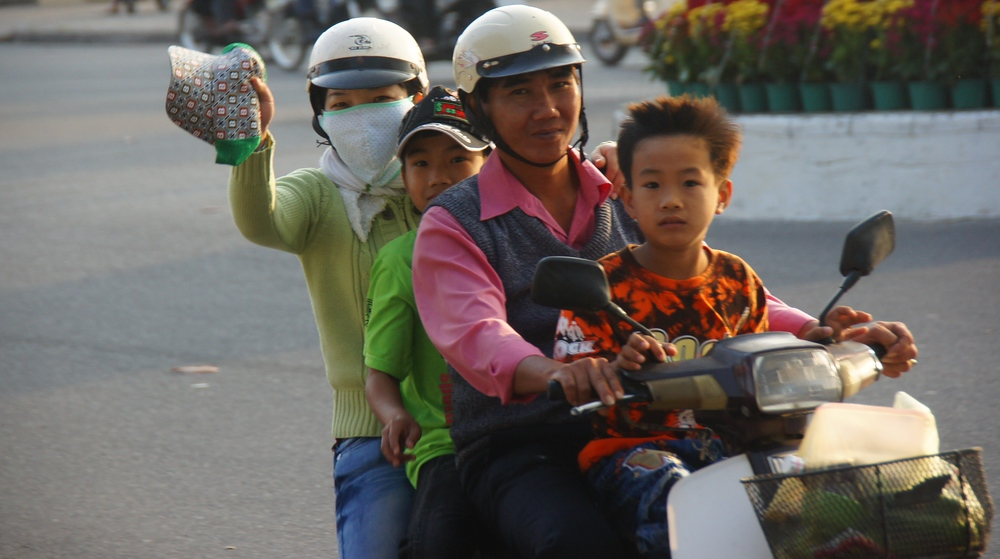 A family of four wave and smile as they speed along the street on their scooter - Nha Trang, Vietnam.