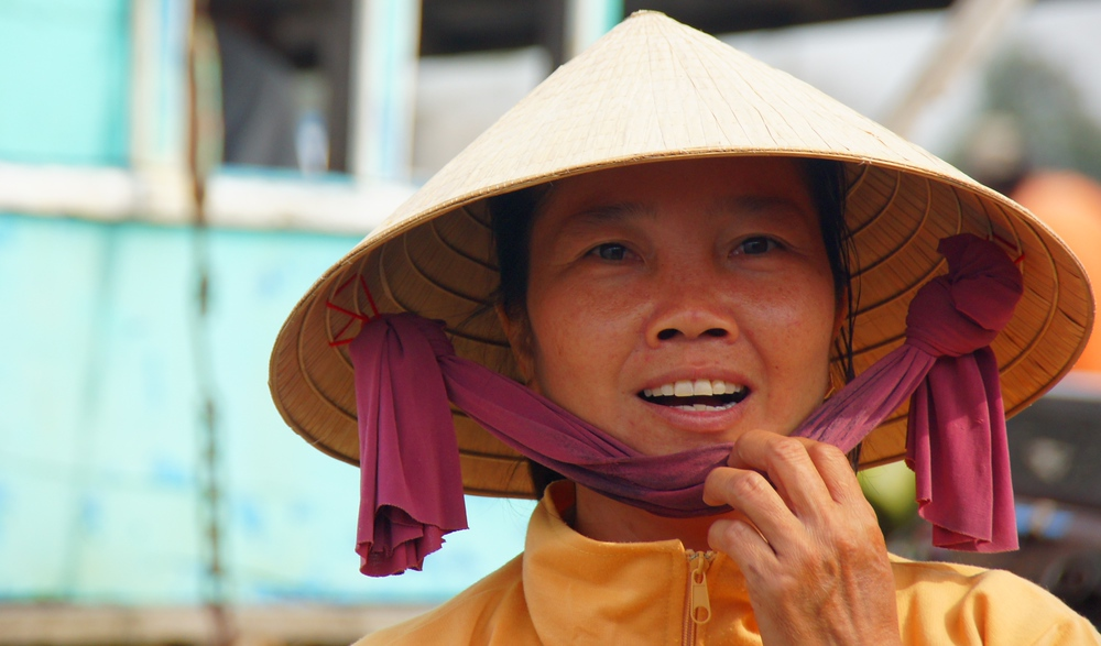 A Vietnamese lady wearing a conical hat adjusts the chin strap while smiling - Mekong Delta, Vietnam.