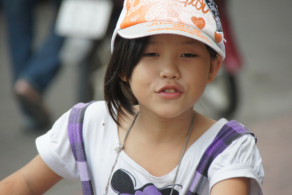 A cute girl stops to pose and briefly smile before taking off on her bicycle - Saigon, Vietnam.