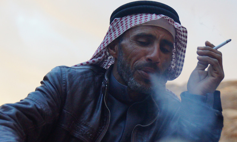 A Bedouin man puffs exhales smoke from a cigarette nearby our camp in Wadi Rum.