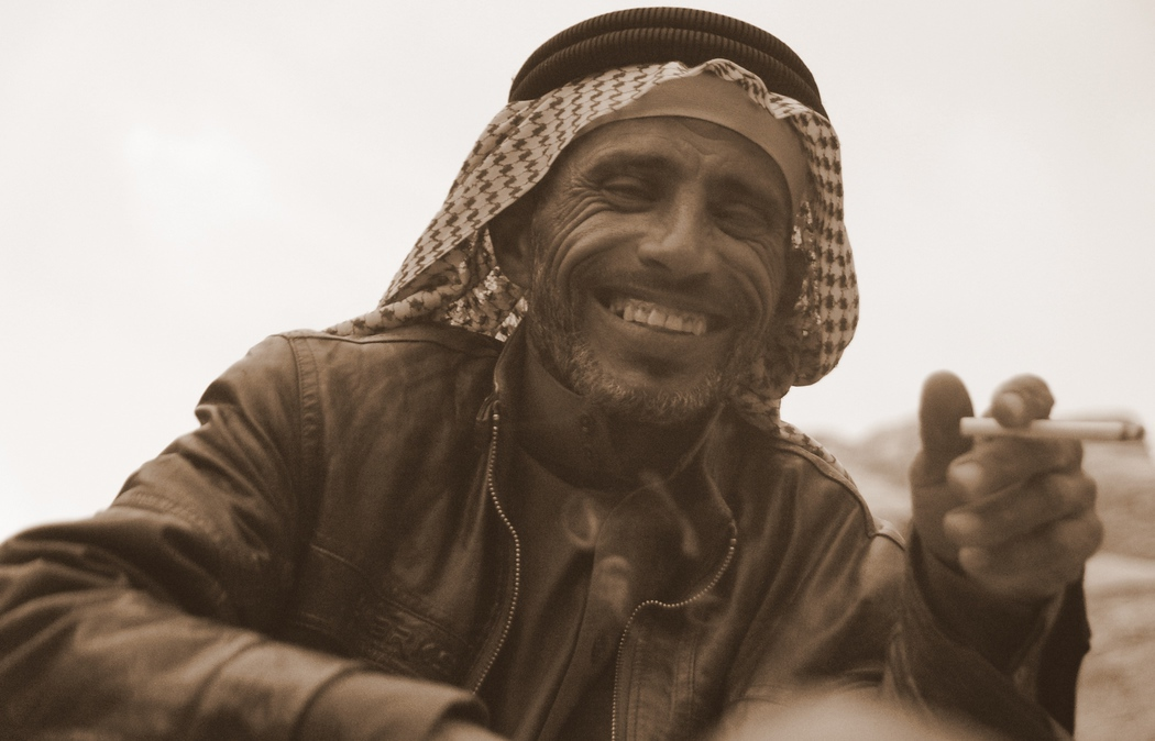 Here is a candid shot of a Bedouin man smoking a cigarette and beaming an even more impressive smile.