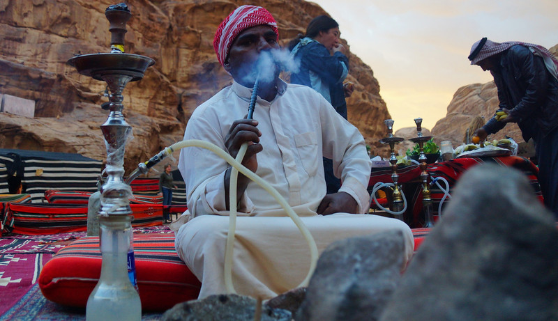 This is another shot of the same Bedouin man from the third photo in this gallery smoking Hookah.  In this particular photo you can clearly notice the smoking device and rock terrain in the background.