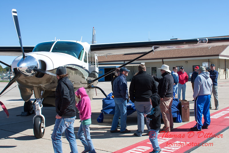 52 - Passengers and baggage near the Air Choice One Caravan on the ramp at the South East Iowa Air Show in Burlington Iowa