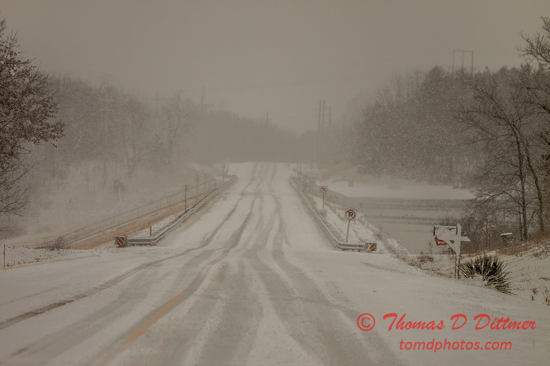# 27 - Snow falling covers the roadway over the dam at Evergreen Lake Hudson Illinois